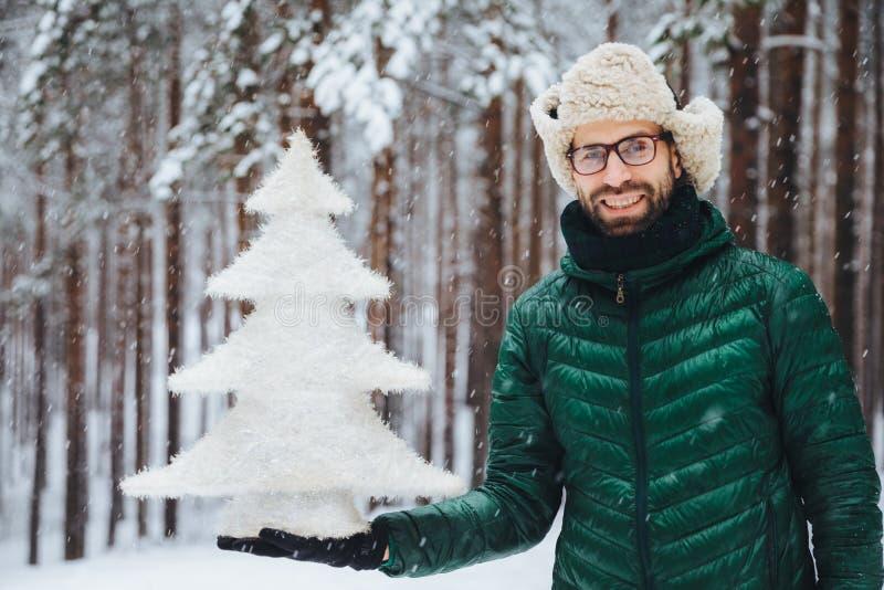 När du ler den positiva mannen bär exponeringsglas, hatt, och anoraken, rymmer det konstgjorda granträdet, ställningar mot träd s arkivbild