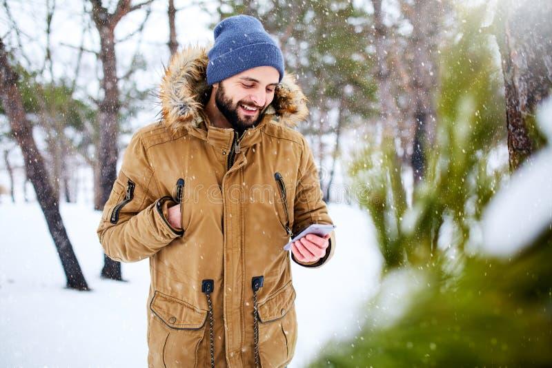 När du ler den skäggiga mannen bär varm kläder och att använda för vinter smartphonen med snabb internetuppkoppling i landssida fotografering för bildbyråer