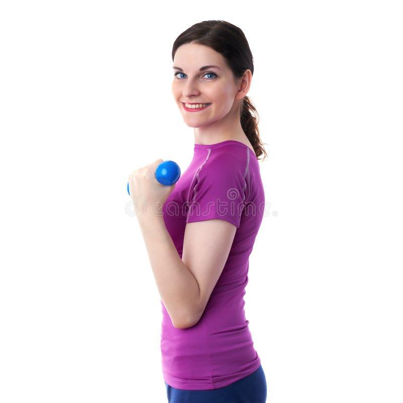När du ler den sportiga kvinnan i violett T-kort over vit isolerade bakgrund royaltyfri fotografi