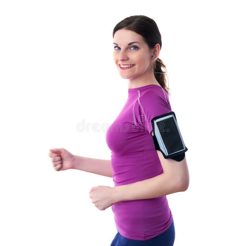 När du ler den sportiga kvinnan i violett T-kort over vit isolerade bakgrund royaltyfri foto