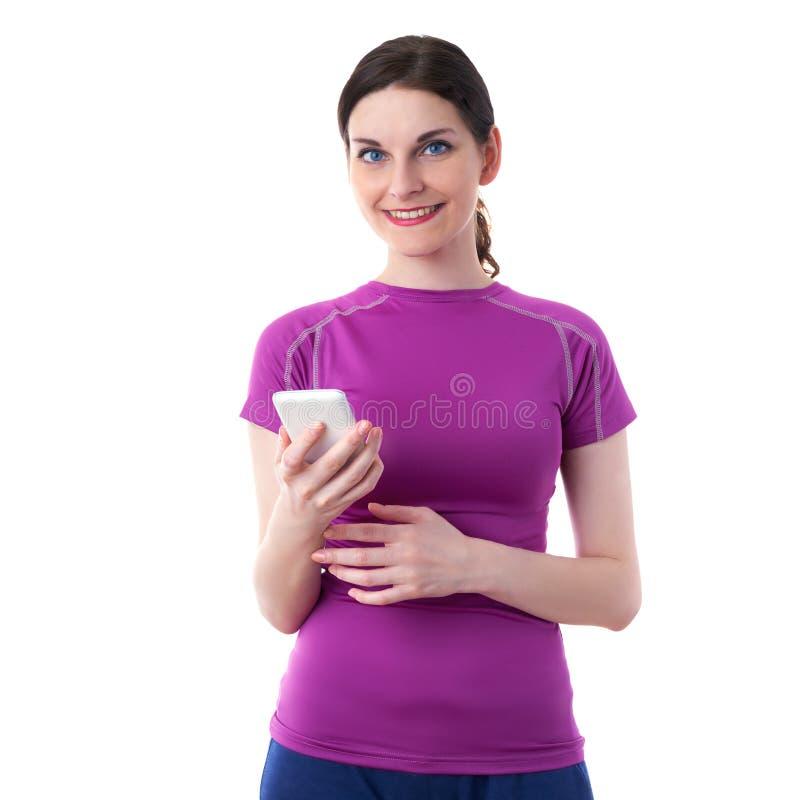 När du ler den sportiga kvinnan i violett T-kort over vit isolerade bakgrund fotografering för bildbyråer