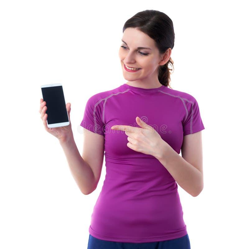 När du ler den sportiga kvinnan i violett T-kort over vit isolerade bakgrund royaltyfri bild