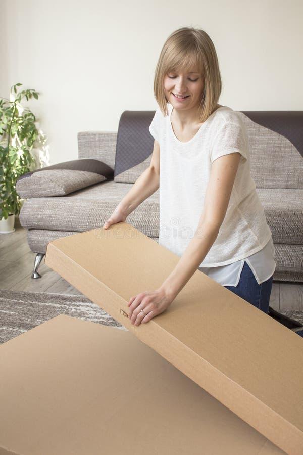 När du ler den unga kvinnan öppnar kartonger i vardagsrummet Soffa och blomma i bakgrunden arkivbilder