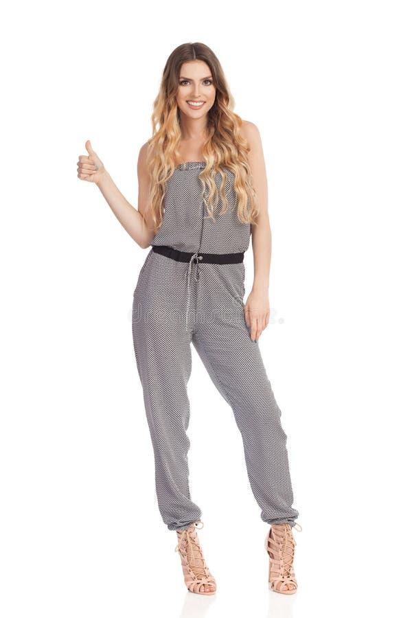 När du ler den unga kvinnan i Jumpsuit visar upp tummen royaltyfri foto