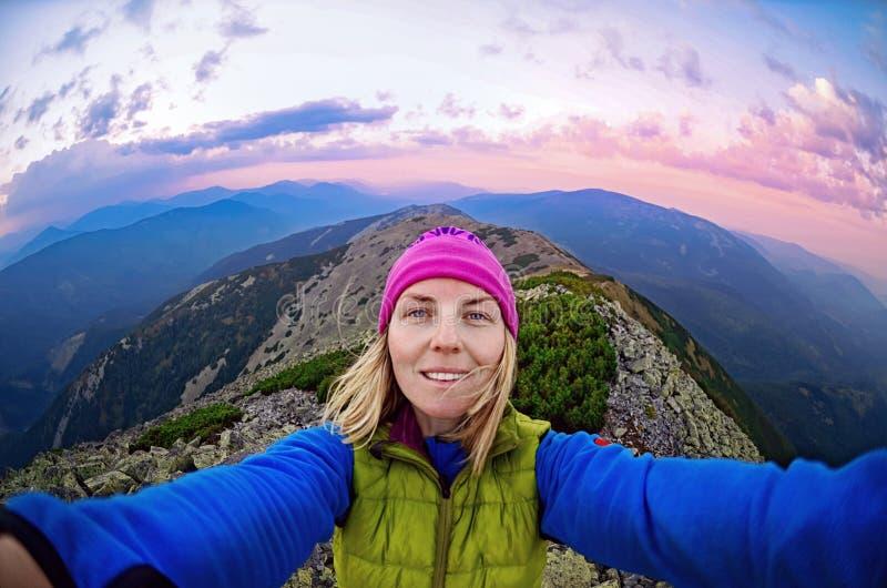 När du ler den unga kvinnan tar en selfie fotografering för bildbyråer