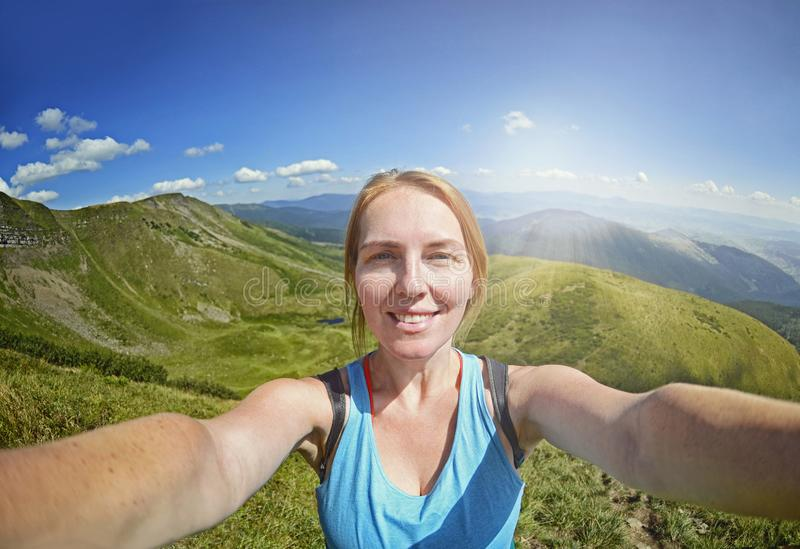 När du ler den unga kvinnan tar en selfie på bergmaximum royaltyfri bild