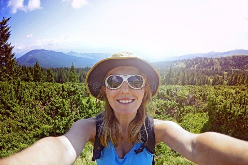 När du ler den unga kvinnan tar en selfie på bergmaximum royaltyfria foton