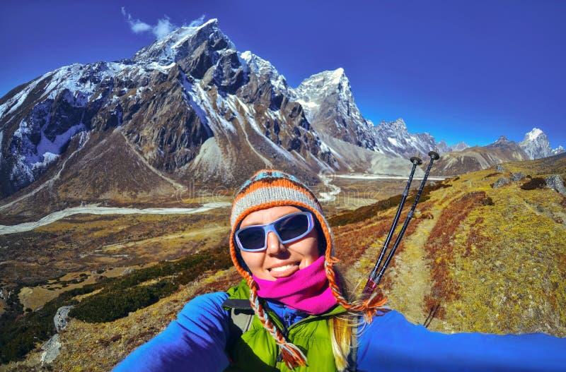 När du ler den unga kvinnan tar en selfie på bergmaximum royaltyfria bilder