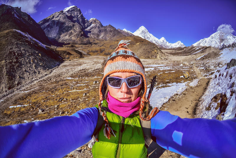 När du ler den unga kvinnan tar en selfie på bergmaximum arkivfoto