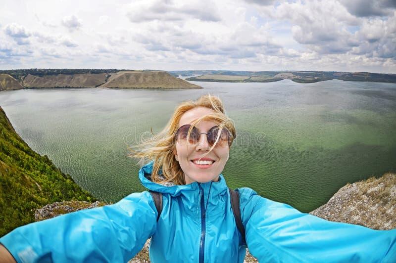 När du ler den unga kvinnan tar en selfie på bergmaximum i Bakota arkivfoton