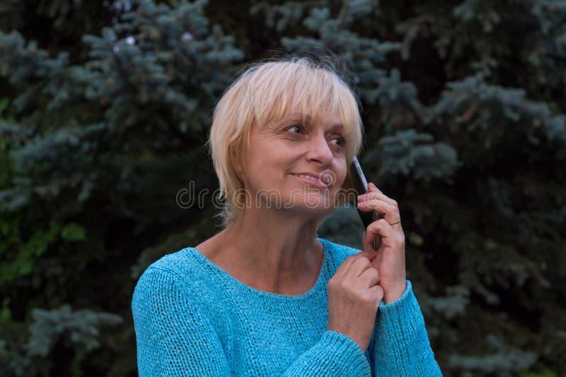 När du ler ellderly kvinnan har en konversation vid telefonen fotografering för bildbyråer
