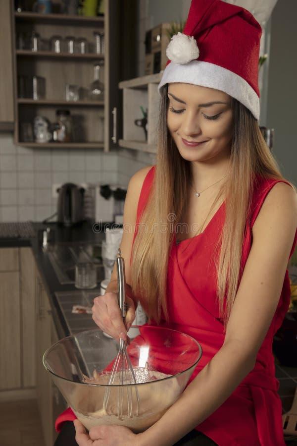När du ler flickan i jul som beklär att sitta på tabellen och, rör kakan, främre sikt arkivfoton
