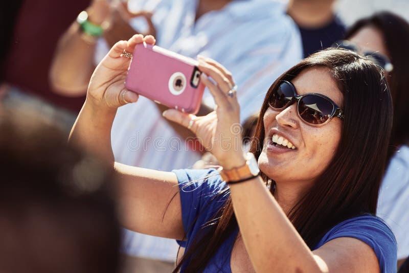 När du ler kvinnan fångar ögonblicket på hennes mobiltelefon fotografering för bildbyråer
