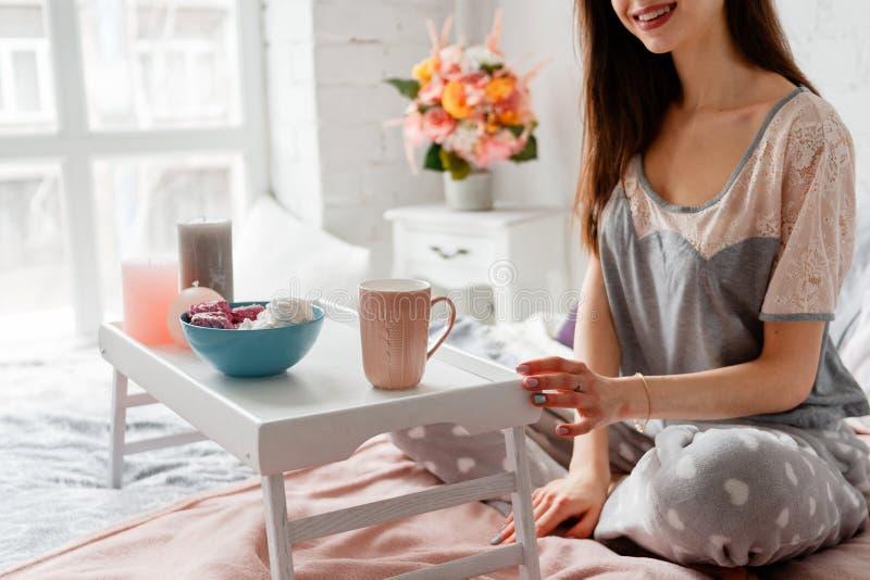 När du ler kvinnan har frukosten i morgonen royaltyfria foton