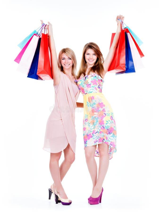 När du ler kvinnor lyftte upp färgrika shoppingpåsar arkivfoto