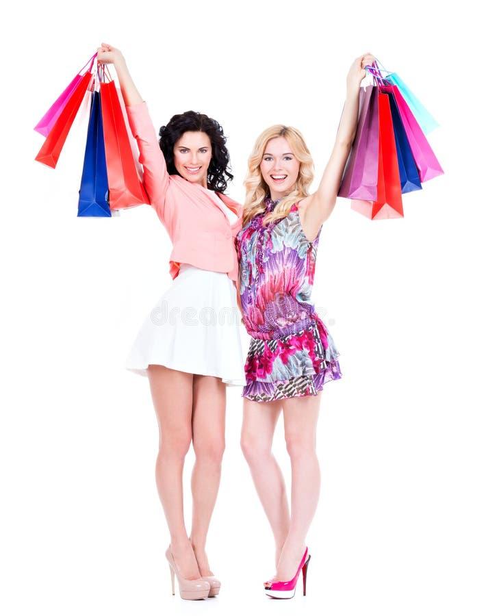 När du ler kvinnor lyftte upp färgrika shoppingpåsar royaltyfria bilder