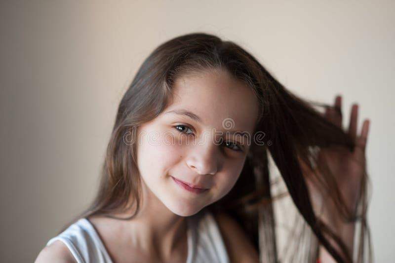 När du ler lilla flickan rätar ut hennes hår med en hand fotografering för bildbyråer