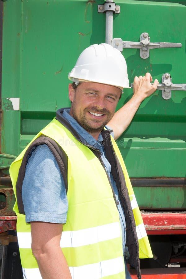 när du ler mannen på en konstruktionsplats öppnar en behållarelastbil arkivbild