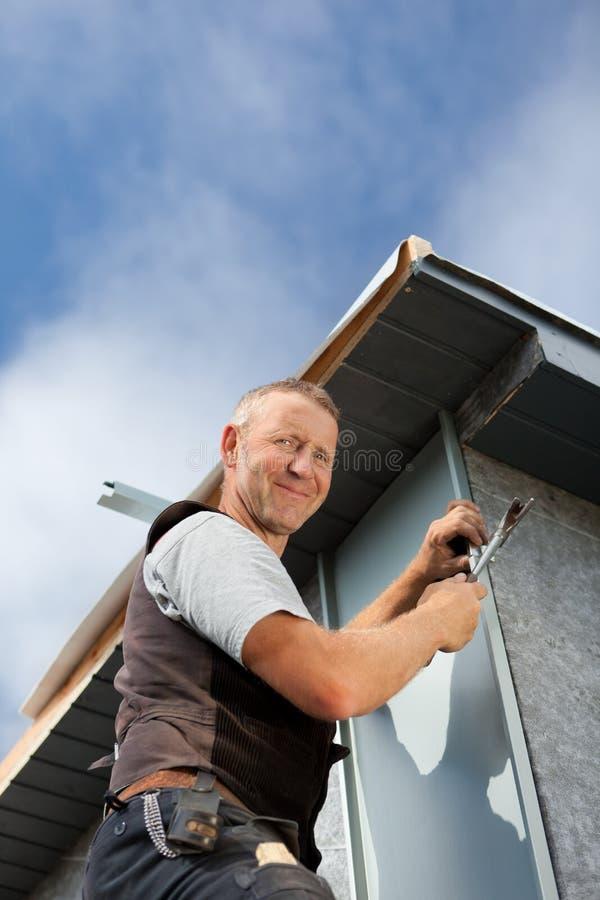 När du ler rooferen monterar ett metallstycke på en vägg arkivfoto