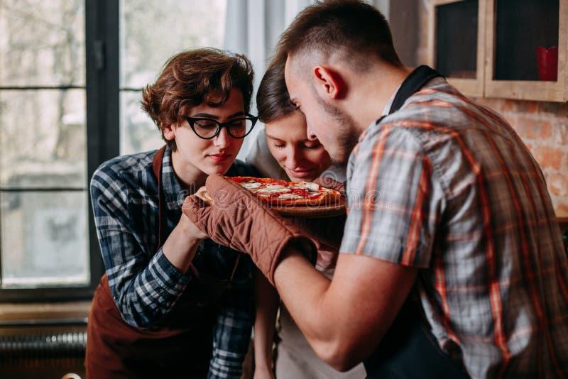 När du ler unga vänner med ögon stängde inhalation av arom av pizza royaltyfri fotografi