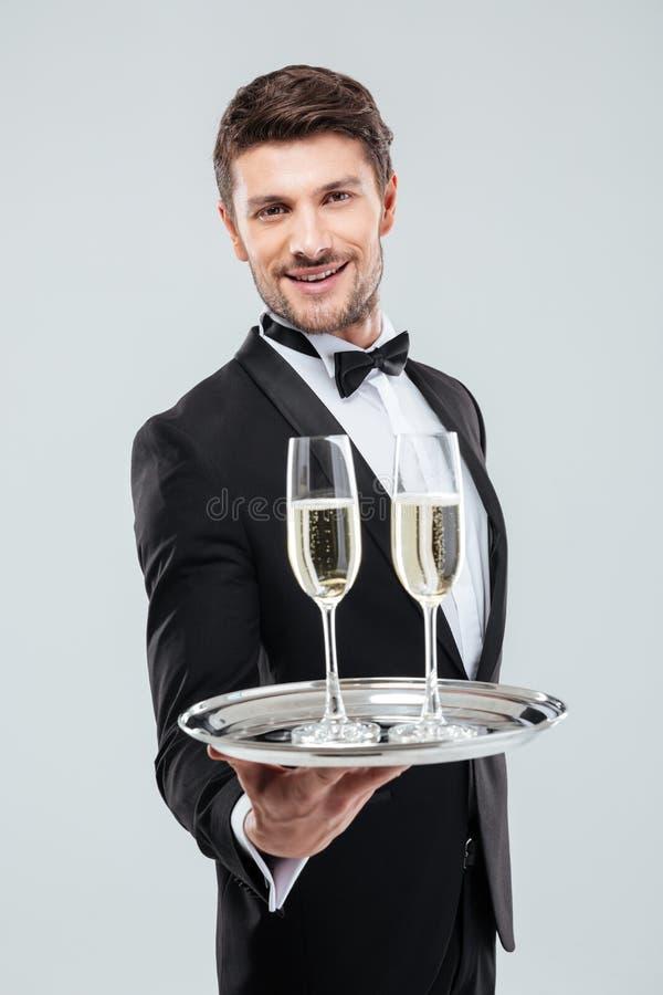 När du ler uppassaren i smoking erbjuder dig exponeringsglas av champagne arkivfoton