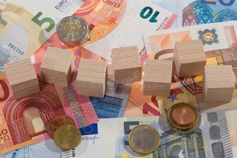 När du ligger sedlar med trä tärnar mynt arkivbilder