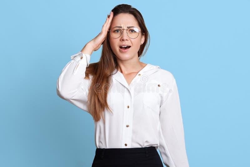 När du oroar den upptagna revisorn rymmer hennes hand på huvudet, minns om viktig arbetsuppgift, öppnar hennes mun med överraskni arkivfoton