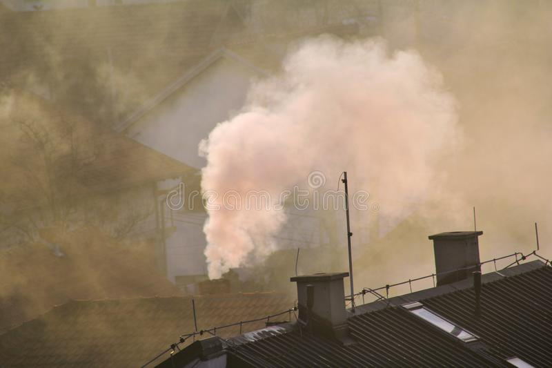 När du röker lampglas på tak av hus sänder ut rök, smog på soluppgång, föroreningar skriver in atmosfär Miljö- katastrof arkivfoton