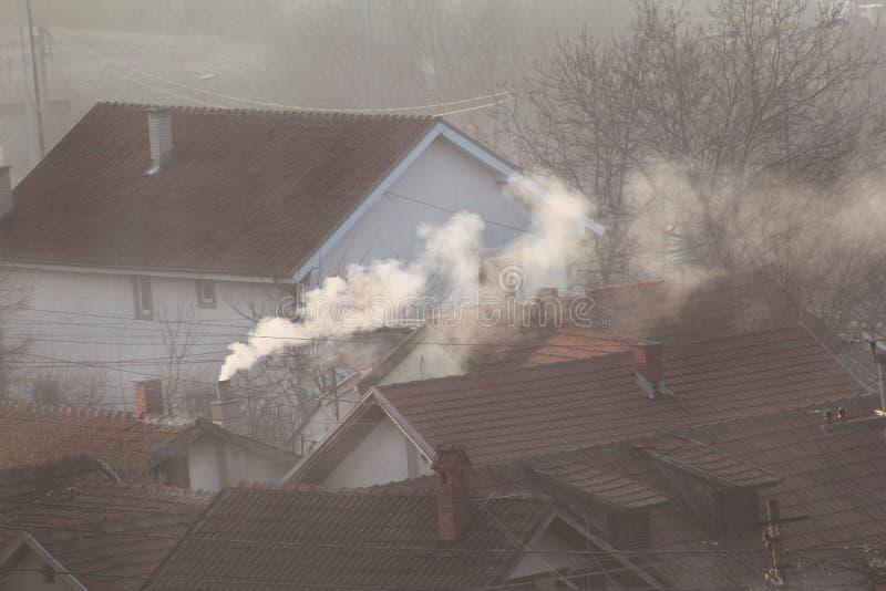 När du röker lampglas på tak av hus sänder ut rök, smog på soluppgång, föroreningar skriver in atmosfär Miljö- katastrof royaltyfri foto