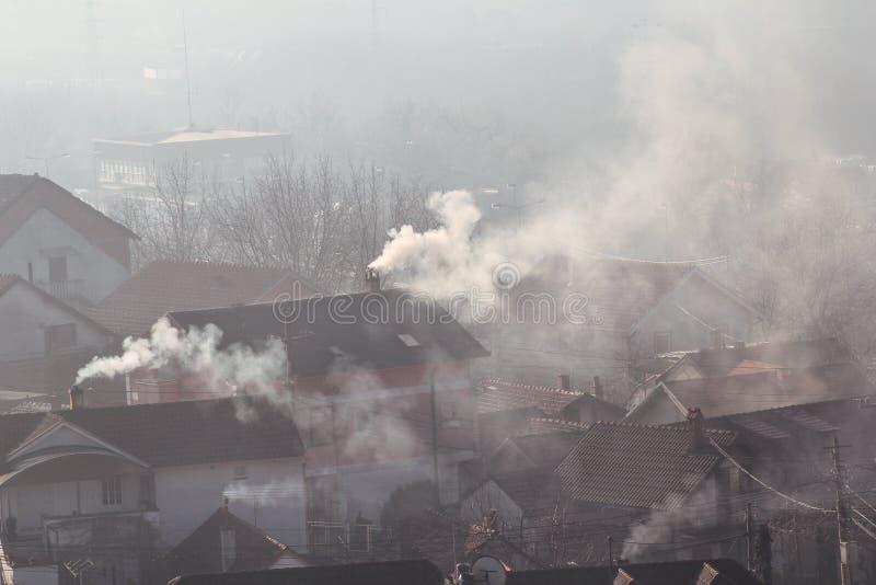 När du röker lampglas på tak av hus sänder ut rök, smog på soluppgång, föroreningar skriver in atmosfär Miljö- katastrof arkivbilder