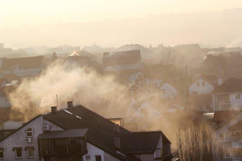 När du röker lampglas på tak av hus sänder ut rök, smog på soluppgång, föroreningar skriver in atmosfär Miljö- katastrof fotografering för bildbyråer