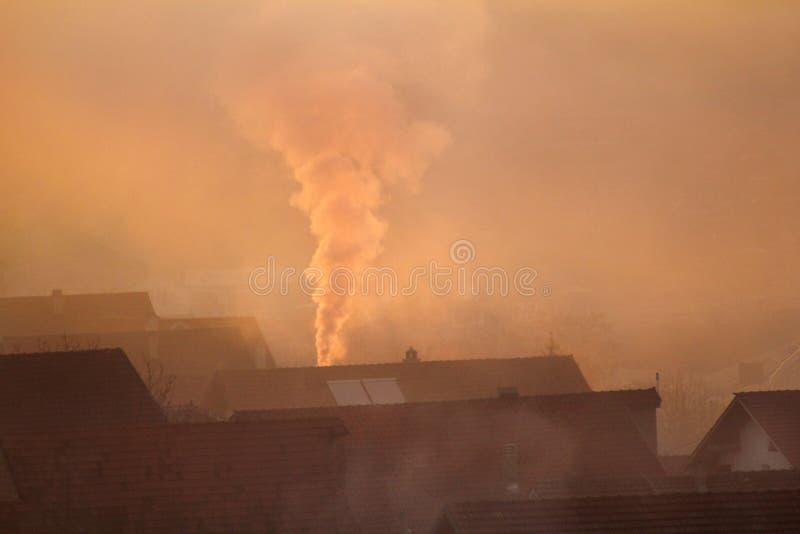 När du röker lampglas på tak av hus sänder ut rök, smog på soluppgång, föroreningar skriver in atmosfär Miljö- katastrof royaltyfria foton