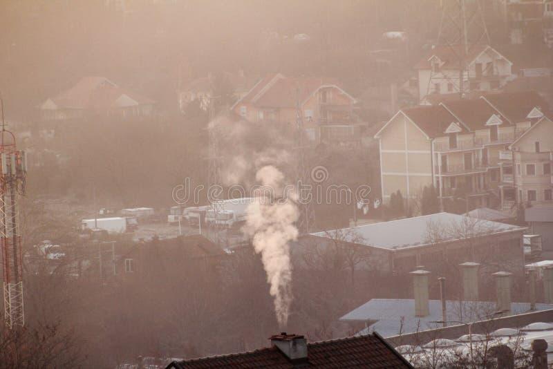 När du röker lampglas på tak av hus sänder ut rök, smog på soluppgång, föroreningar skriver in atmosfär Miljö- katastrof royaltyfria bilder