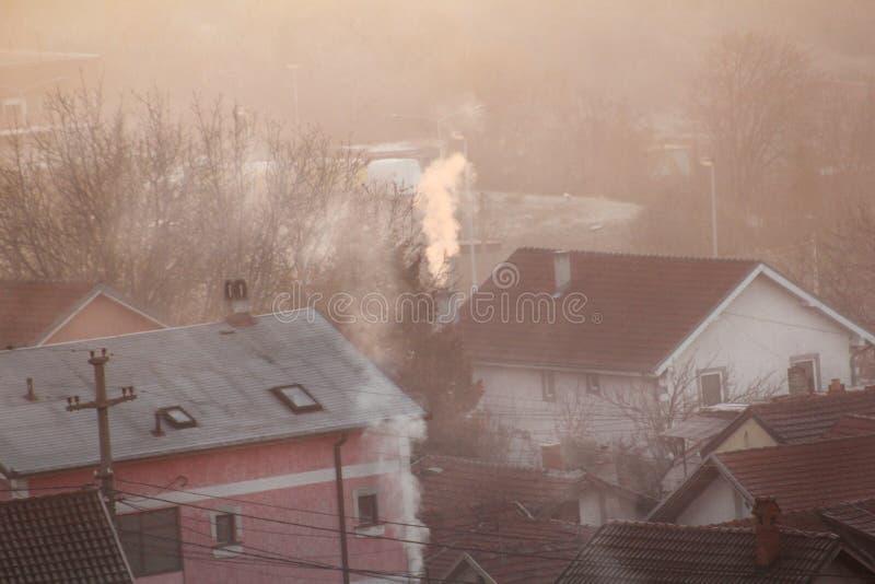 När du röker lampglas på tak av hus sänder ut rök, smog på soluppgång, föroreningar skriver in atmosfär Miljö- katastrof arkivbild