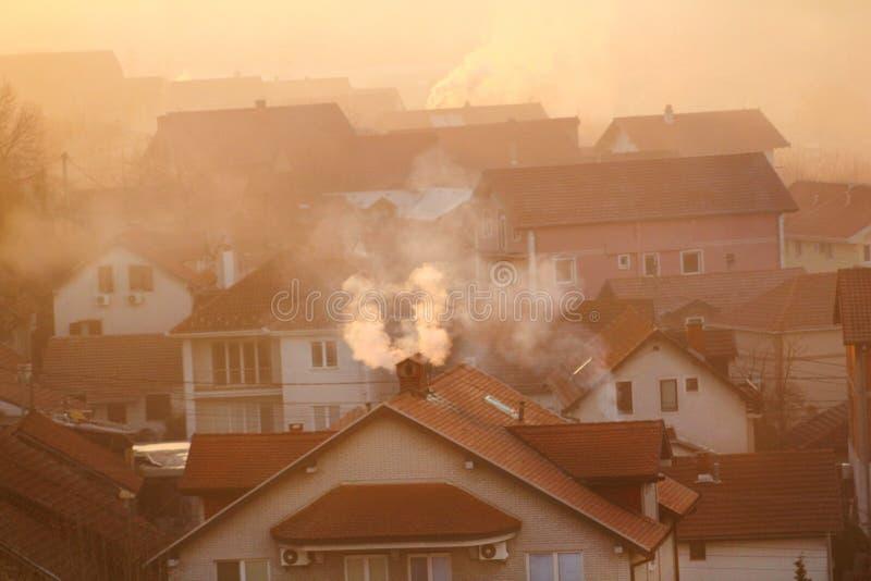När du röker lampglas på tak av hus sänder ut rök, smog på soluppgång, föroreningar skriver in atmosfär Miljö- katastrof royaltyfri fotografi