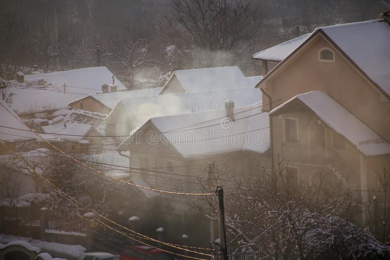 När du röker lampglas på tak med snö av hus sänder ut rök, smog på soluppgång, föroreningar skriver in atmosfär Miljö- katastrof arkivfoton