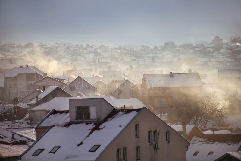 När du röker lampglas på tak med snö av hus sänder ut rök, smog på soluppgång, föroreningar skriver in atmosfär Miljö- katastrof royaltyfri bild
