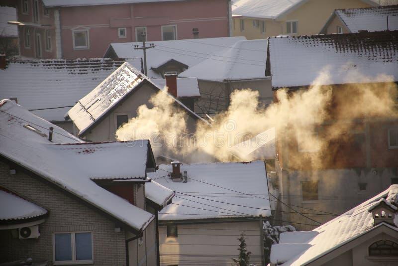 När du röker lampglas på tak med snö av hus sänder ut rök, smog på soluppgång, föroreningar skriver in atmosfär Miljö- katastrof royaltyfri foto
