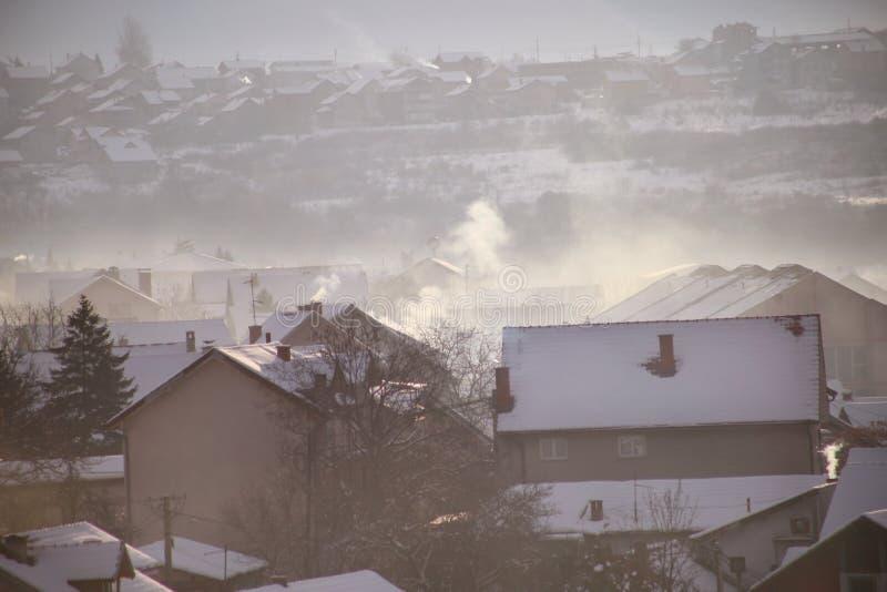 När du röker lampglas på tak med snö av hus sänder ut rök, smog på soluppgång, föroreningar skriver in atmosfär Miljö- katastrof arkivbild
