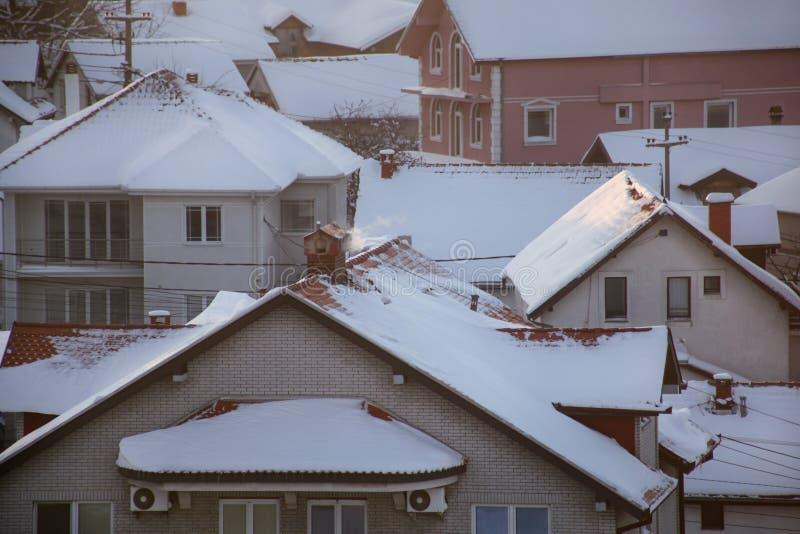 När du röker lampglas på tak med snö av hus sänder ut rök, smog på soluppgång, föroreningar skriver in atmosfär Miljö- katastrof arkivbilder