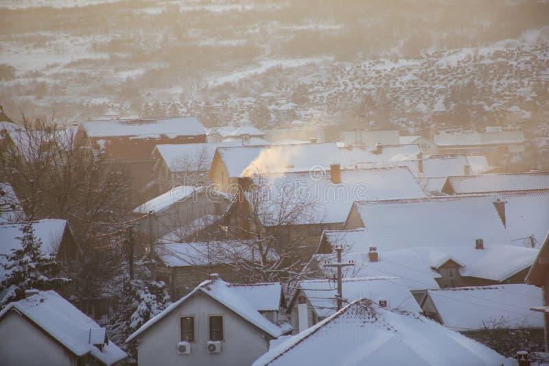 När du röker lampglas på tak med snö av hus sänder ut rök, smog på soluppgång, föroreningar skriver in atmosfär Miljö- katastrof fotografering för bildbyråer