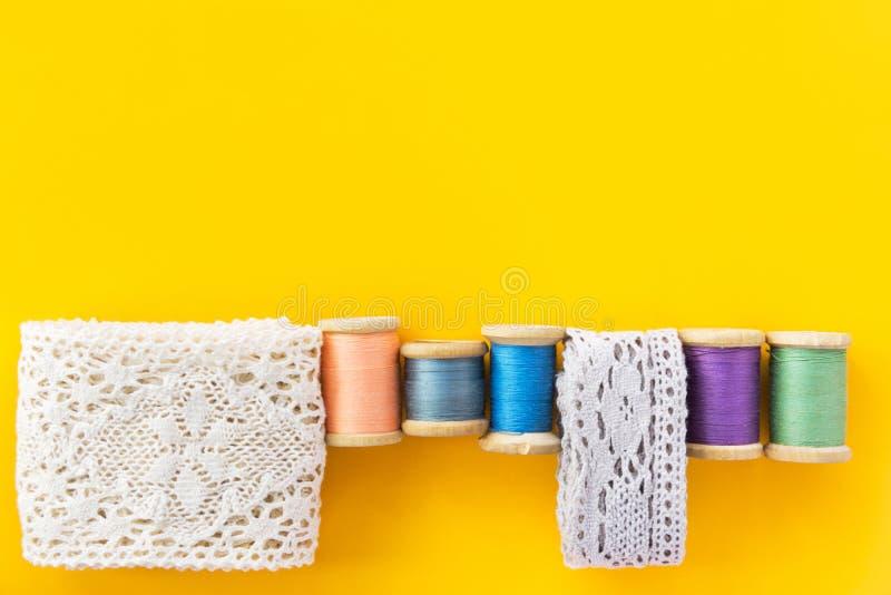 När du syr hantverk som hobbyer danar klädbakgrund med vit bomullsspets, rullar trätappningrullar med mångfärgade trådar royaltyfri foto