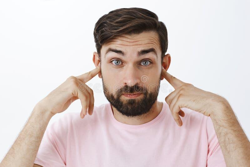Nära öron för skäggig caucasian man som att stå i det höga fullsatta stället som rymmer pekfingrar i earholes som trutar och arkivfoto