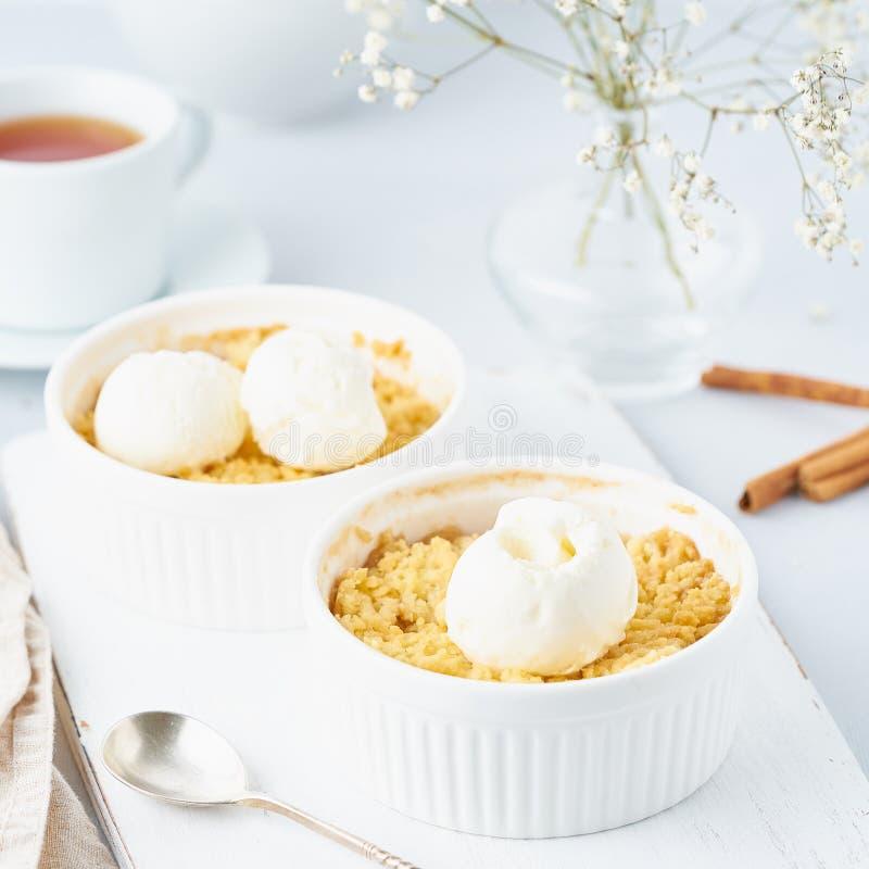 Nära övre äpplesmulpaj med glass, sked med streusel Sidosikt, lodlinje Morgonfrukost på ett ljust - grå tabell royaltyfria bilder