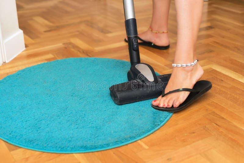 Nära övre användande dammsugare för kvinna hemma royaltyfri foto
