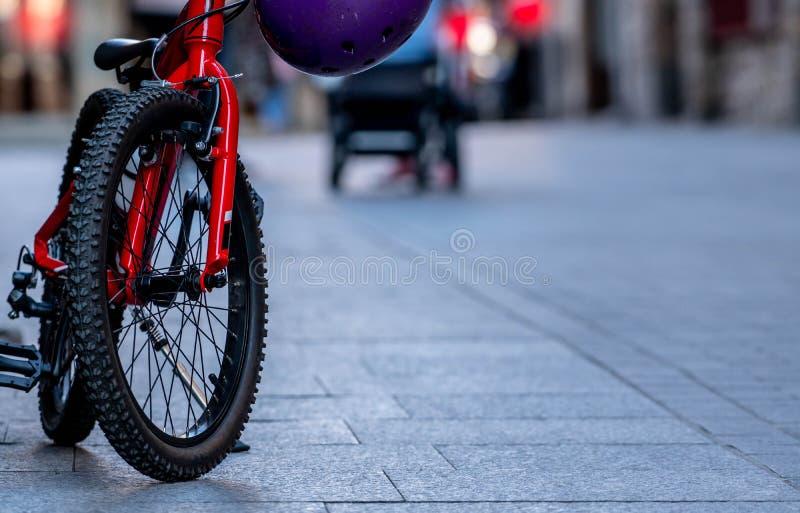 Nära övre barncykel som parkeras på vägen i stad Röd cykel med svarta hjul Unges cykel arkivbilder