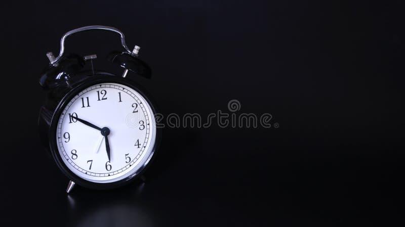 Nära övre bild av den gamla svarta tappningringklockan 10 minuter för sex klockan royaltyfria foton