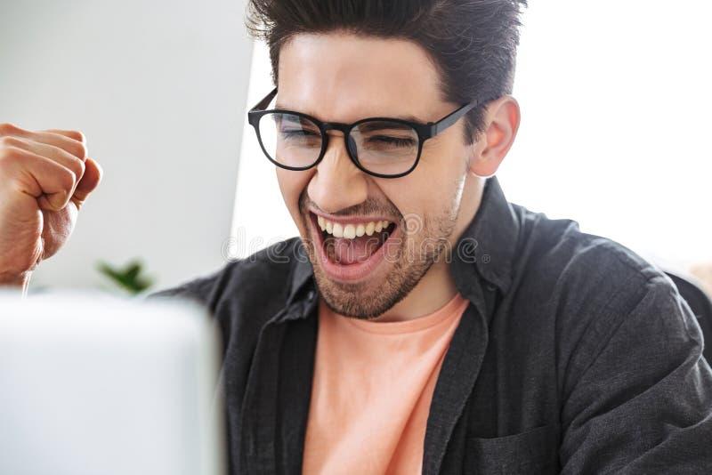 Nära övre bild av den gladlynta stiliga mannen i glasögon royaltyfri fotografi