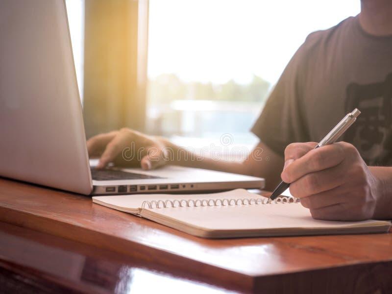 Nära övre bild av den unga mannen som använder bärbar datorteknologi och skriver anteckningsbokarbetsplatsbegrepp royaltyfria bilder