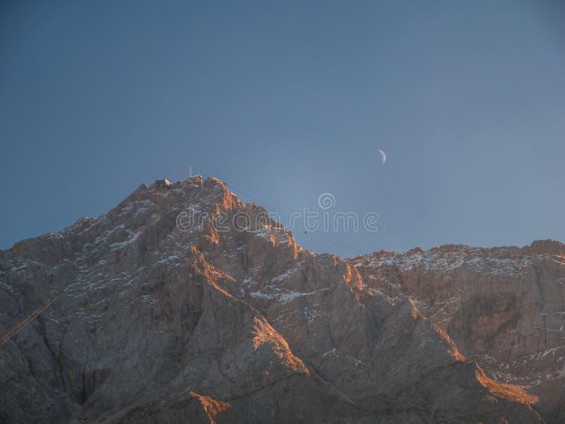Nära övre bild av den Zugspitze Tyskland högsta berg med månen och gondolen arkivfoto